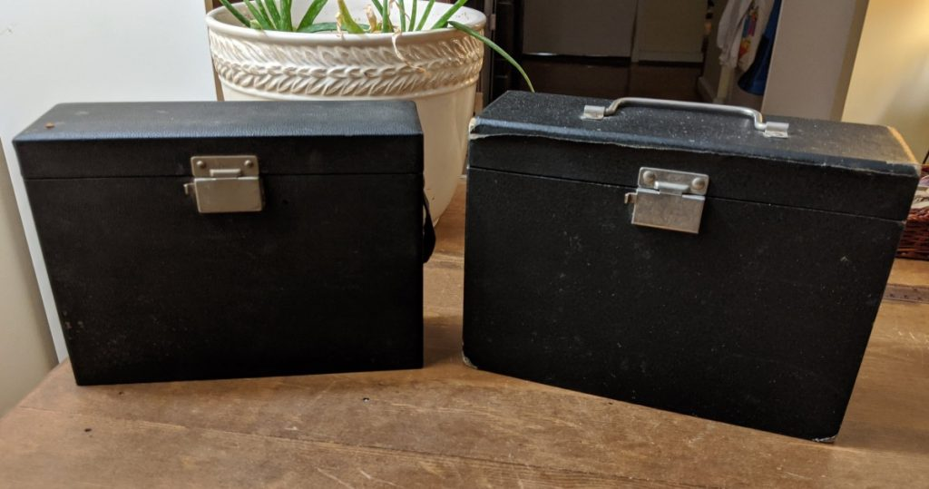 Two black oblong hinged cases
